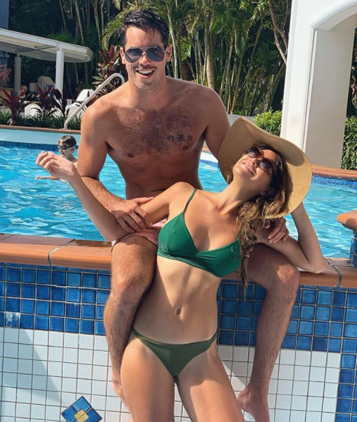 Jake Ellis and Megan Marx wearing swimwear at a pool