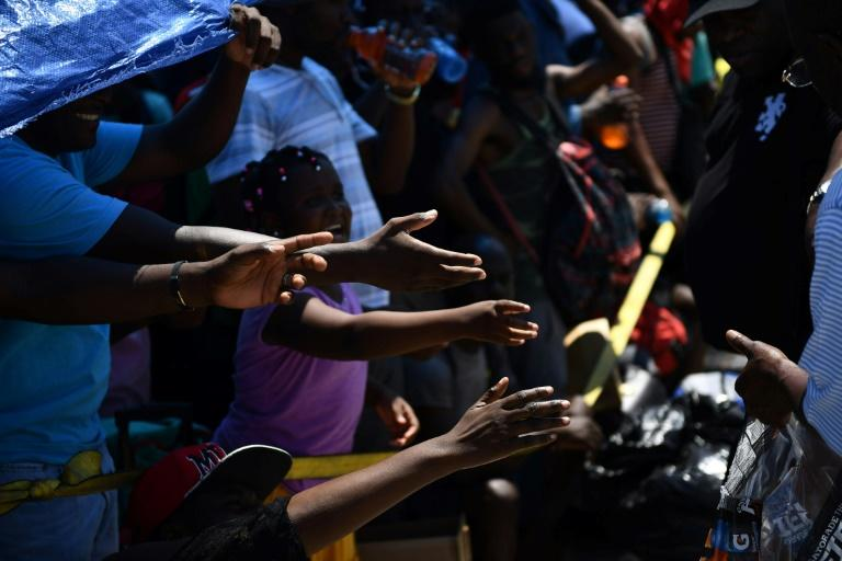 People reach out for beverages as they await evacuation in Marsh Harbour in the Bahamas (AFP Photo/Brendan Smialowski)