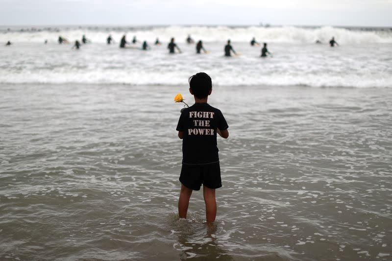 A boy holds a rose as he watches surfers at The Black Girls Surf paddle-out in memory of George Floyd,who died in Minneapolis police custody, in Santa Monica