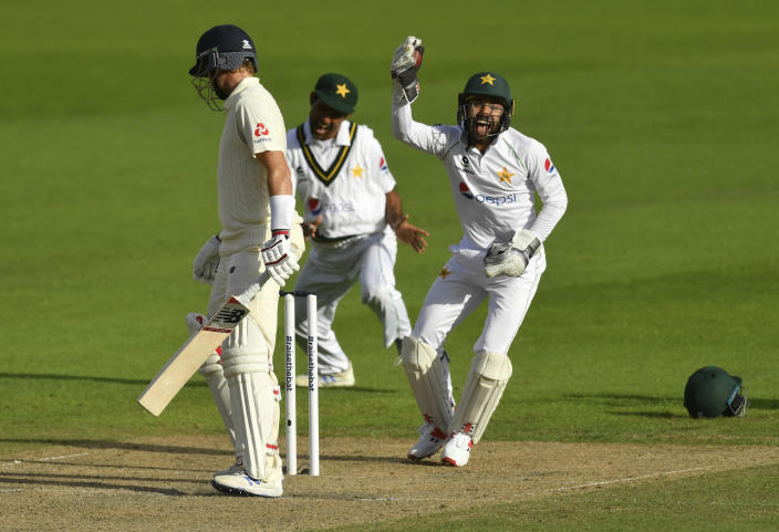 Pakistan's wicketkeeper Mohammad Rizwan, right, celebrates after taking the catch to dismiss England's captain Joe Root, left, during the second day of the first cricket Test match between England and Pakistan at Old Trafford in Manchester, England, Thursday, Aug. 6, 2020. (Dan Mullan/Pool via AP)