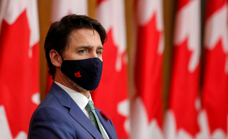 Canadian Prime Minister Justin Trudeau listens while wearing a mask at a news conference in Ottawa