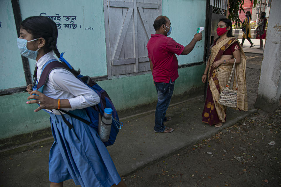 An employee checks the temperature of a teacher as schools in north-eastern Assam state reopen after being closed for months due to the coronavirus pandemic in Gauhati, India, Monday, Nov. 2, 2020. (AP Photo/Anupam Nath)