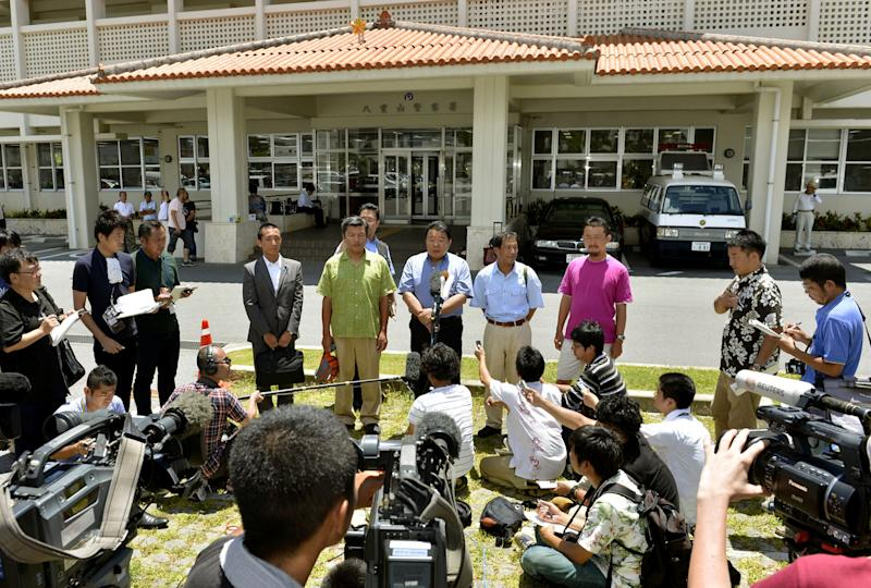 Japanese activists, center, who landed on Uotsuri island Sunday, speak to the media after they were questioned by the authorties at a police station in Ishigaki city, Okinawa prefecture, Japan. An unauthorized landing by the Japanese activists on the island at the center of a dispute with China is sparking nationalist outrage and fueling calls on both sides for aggressive government action that some fear could lead to an escalation of tensions. Japanese authorities on Monday, questioned the 10 Japanese, including five local assembly members, who swam ashore on the disputed island the day before. (AP Photo/Kyodo News, File) JAPAN OUT, MANDATORY CREDIT, NO LICENSING IN CHINA, HONG KONG, JAPAN, SOUTH KOREA AND FRANCE