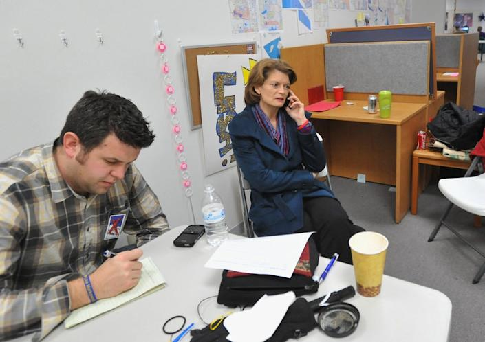 Sen. Lisa Murkowski, right, a longtime proponent of oil and gas drilling in ANWR, speaks on the phone at her campaign headquarters, with Steve Wackowski at left.