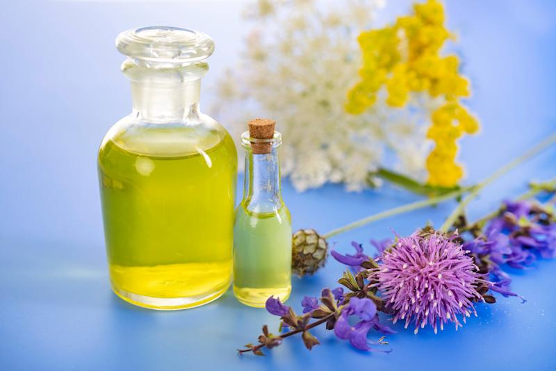 bottles of essential oils surrounded by flowers.