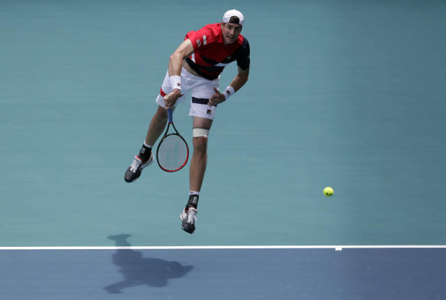 John Isner serves to Felix Auger-Aliassime, of Canada, during their semifinal match at the Miami Open tennis tournament, Friday, March 29, 2019, in Miami Gardens, Fla. (AP Photo/Lynne Sladky)