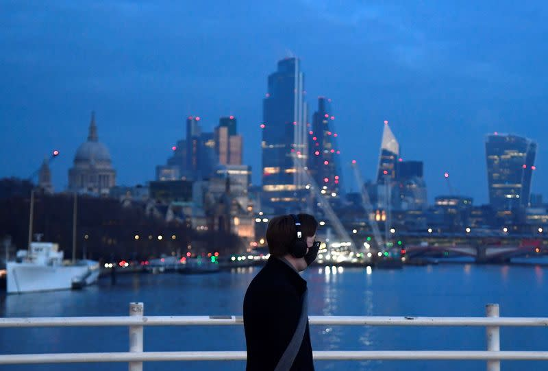 A man looks towards skyscrapers of the City of London financial district as he crosses Waterloo Bridge in London
