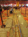 A worker inspects electrical cables on the casino floor of Bally's casino in Atlantic City N.J., Monday, June 14, 2021. The new owners of Bally's Atlantic City are attempting to revive a comatose casino in perhaps the most cutthroat gambling market in America. Rhode Island-based Bally's Corporation is spending at least $90 million on the Boardwalk casino over the next five years, including hotel room makeovers, a renovation of the casino floor, new slot machines and restaurants, and more live entertainment. (AP Photo/Wayne Parry)