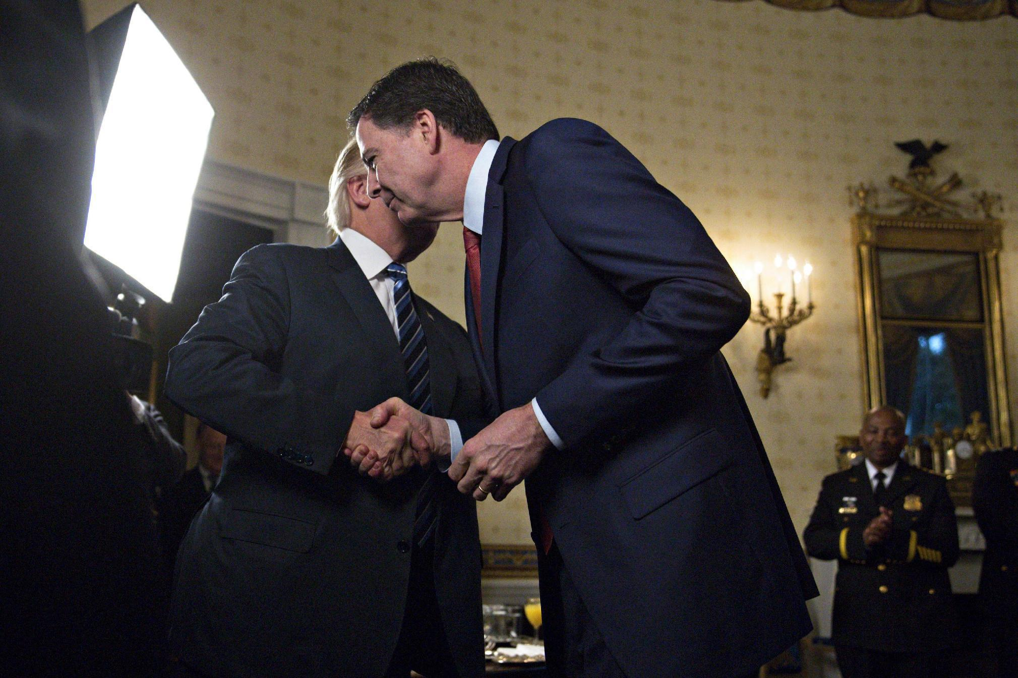 U.S. President Donald Trump (L) shakes hands with James Comey, director of the Federal Bureau of Investigation (FBI), during an Inaugural Law Enforcement Officers and First Responders Reception in the Blue Room of the White House on January 22, 2017 in Washington, DC. (Photo by Andrew Harrer-Pool/Getty Images)