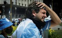 A fan cries after paying tribute to late Argentine football legend Diego Maradona as the funeral cortege leaves the presidential palace for the cemetery, in Buenos Aires, on November 26, 2020