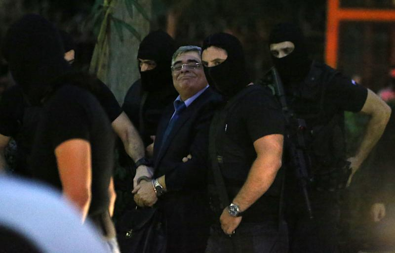 Leader of the extreme far-right Golden Dawn party, Nikos Michaloliakos, center, smiles to his supporters as he escorted by anti-terror police upon his arrival to a court for a preliminary hearing into charges of participating in a criminal organization in Athens, Wednesday, Oct. 2, 2013. Three lawmakers from Greece's extremist right-wing Golden Dawn party were released from custody Wednesday pending trial, after they provided initial testimony in criminal investigation triggered by the slaying of a left-wing rapper. A fourth lawmaker, Ioannis Lagos, was jailed pending trial (AP Photo/Thanassis Stavrakis)