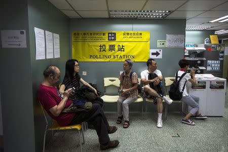 People wait to vote at a polling station during an last day of civil referendum held by the Occupy Central organisers in Hong Kong