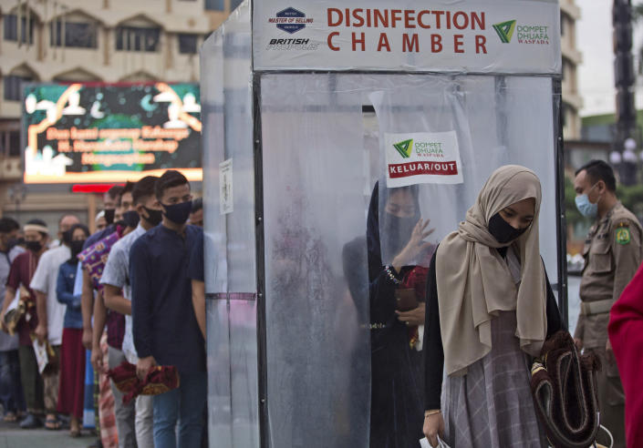 """Muslims queue up to enter a disinfection chamber set up as a precaution against the new coronavirus outbreak, prior to entering Al Mashun Grand Mosque's compound to attend an Eid al-Adha prayer in Medan, North Sumatra, Indonesia, Friday, July 31, 2020. Eid al-Adha, or """"Feast of the Sacrifice,"""" is a holiday which honors the prophet Ibrahim, or Abraham, as he is known in the Bible, for his willingness to sacrifice his son on the order of God who was testing his faith. (AP Photo/Binsar Bakkara)"""