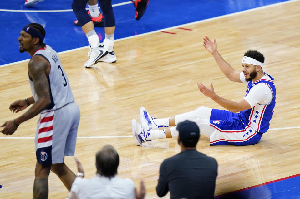 Philadelphia 76ers' Seth Curry, right, reacts after a foul by Washington Wizards' Bradley Beal, left, during the second half of Game 5 in a first-round NBA basketball playoff series, Wednesday, June 2, 2021, in Philadelphia. (AP Photo/Matt Slocum)
