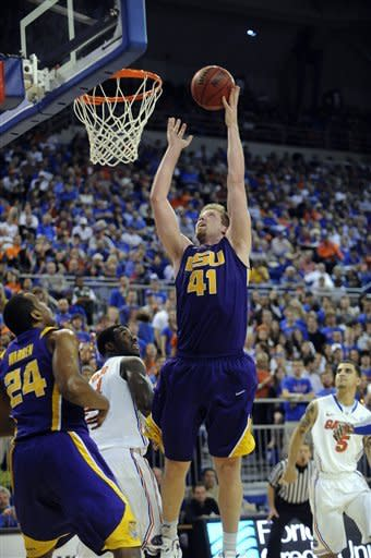 LSU's Justin Hamilton (41) goes over Florida's Patric Young (4) to score two points as his teammate Storm Warren (24) watches his shot during the second half of an NCAA college basketball game in Gainesville, Fla., Saturday, Jan. 21, 2012. Florida took the win over LSU with a score of 76-64. (AP Photo/Phil Sandlin)