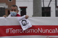 """A man helps hold up a banner with a hashtag that reads in Spanish; """"Terrorism never again"""" as he joins others outside the anti-terrorism directorate to celebrate the death of Abimael Guzman, founder and leader of the Shining Path guerrilla movement, in Lima, Peru, Saturday, Sept. 11, 2021. Guzman who was captured in 1992, died on Saturday in a military hospital after an illness, the Peruvian government said. He was 86. (AP Photo/Martin Mejia)"""