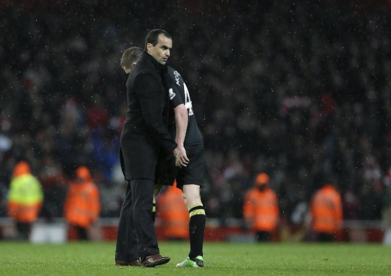 Wigan Athletic's manager Roberto Martinez consoles his player James McCarthy after Wigan were relegated from the Premier League as they lost 4-1 to Arsenal following their English Premier League soccer match at Arsenal's Emirates stadium in London, Tuesday, May  14, 2013. (AP Photo/Alastair Grant)