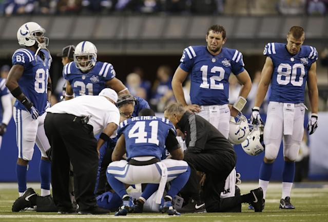 Indianapolis Colts players gather around as trainers talk to Indianapolis Colts wide receiver Reggie Wayne (87) after Wayne injures his knee during the second half of an NFL football game, Sunday, Oct. 20, 2013, in Indianapolis. (AP Photo/AJ Mast)