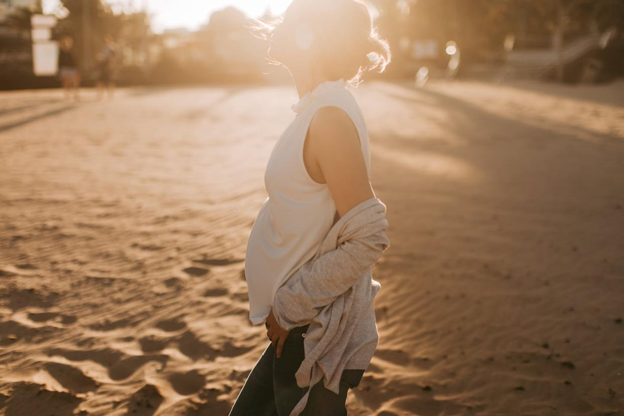 Photo of a young woman enjoying pregnancy while walking down the beach on sunset