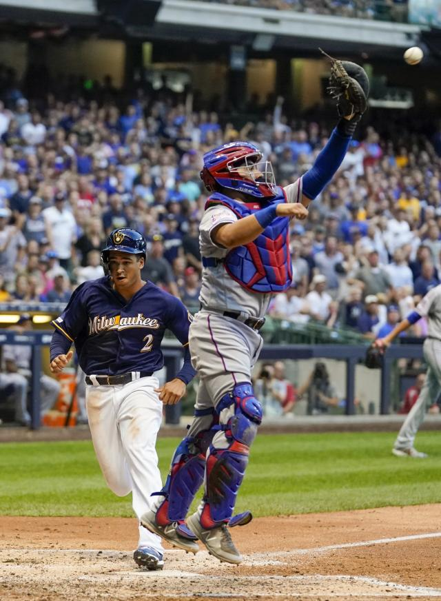 Milwaukee Brewers' Trent Grisham scores past Texas Rangers catcher Jose Trevino during the fourth inning of a baseball game Saturday, Aug. 10, 2019, in Milwaukee. Grisham scored from second on a hit by Mike Moustakas. (AP Photo/Morry Gash)
