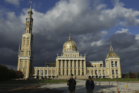 FILE PHOTO: Workers walk in front of Poland's largest Roman Catholic church and one of the largest in the world, Basilica of Our Lady of Lichen, in Lichen Stary