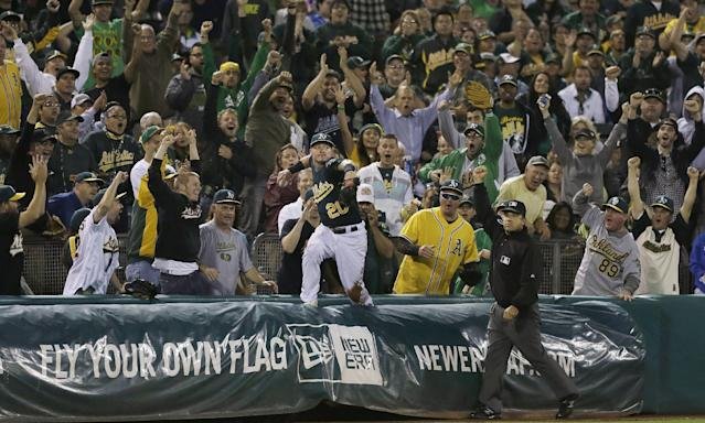 Oakland Athletics third baseman Josh Donaldson (20) looks to throw the ball after catching a foul ball into the seats by Texas Rangers' David Murphy during the sixth inning of a baseball game in Oakland, Calif., Tuesday, Sept. 3, 2013. Third base umpire Phil Cuzzi, right, makes thecall as fans cheer. (AP Photo/Jeff Chiu)
