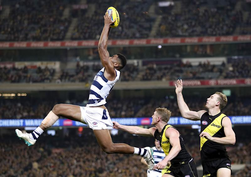 Esava Ratugolea of the Cats marks the ball ahead of Josh Caddy of the Tigers and Tom Lynch of the Tigers during the 2019 AFL round 12 match between the Richmond Tigers and the Geelong Cats at the Melbourne Cricket Ground.