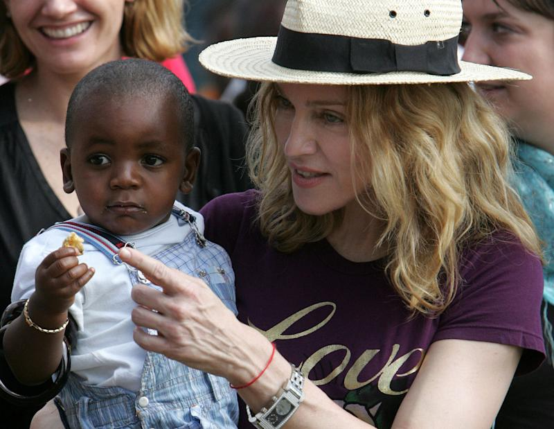 FILE-  In this April 19, 2007 file photo, U.S. singer Madonna carries her Malawian adopted son David Banda at Consol Homes, a day care center that she is funding in the village of Masekese, Malawi. Madonna, who has adopted two children from Malawi, arrived back in the country at 9am local time, Sunday, April 1, 2013, according to Kamuzu International Airport (KIA) immigration officials in the capital, Lilongwe. (AP Photo/Karel Prinsloo, file)