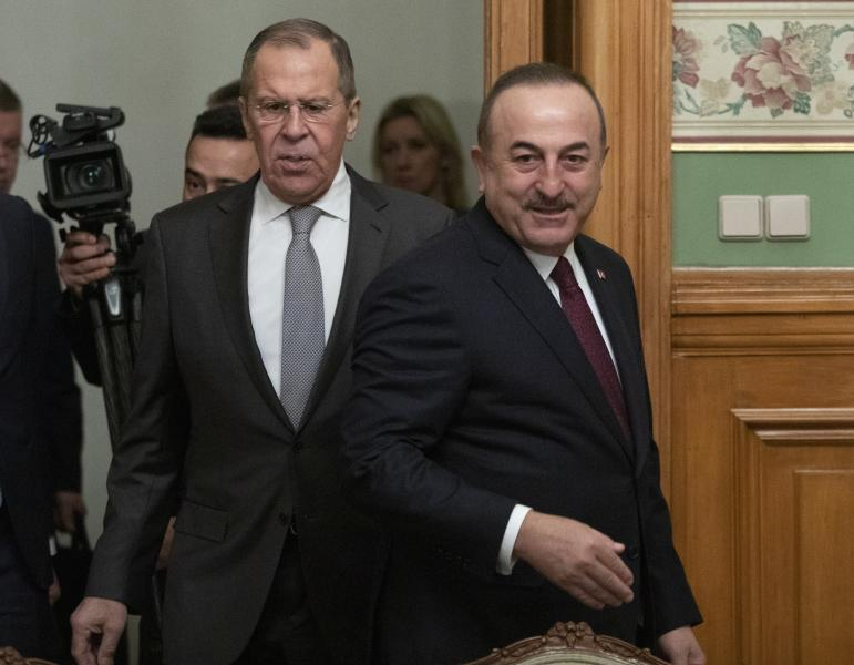 Turkish Foreign Minister Mevlut Cavusoglu, right, and Russian Foreign Minister Sergey Lavrov enter a hall for the talks in Moscow, Russia, Monday, Jan. 13, 2020. Foreign and defense ministers of Russia and Turkey met as part of an effort by Moscow and Ankara to sponsor Monday's talks between rival parties in Libya in the Russian capital. (AP Photo/Pavel Golovkin, Pool)