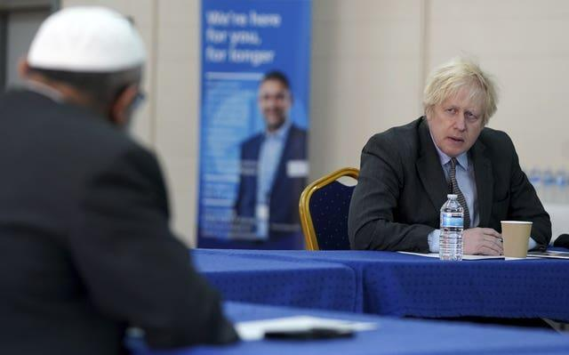 Prime Minister Boris Johnson speaks to members of staff during a visit to a coronavirus vaccination centre in Batley, West Yorkshire (Jon Super/PA)