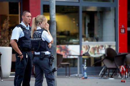 Police stand outside where a 21-year-old Syrian refugee killed a woman with a machete in Reutlingen