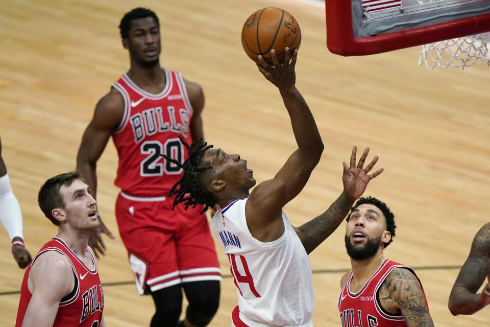 Los Angeles Clippers guard Terance Mann, center, shoots as Chicago Bulls forward Luke Kornet, left, guard Denzel Valentine, right, and guard Adam Mokoka watch during the second half of an NBA basketball game in Chicago, Friday, Feb. 12, 2021. (AP Photo/Nam Y. Huh)