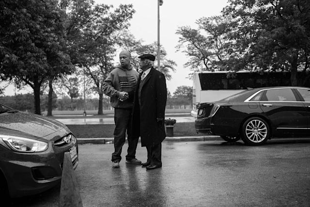 <p>Spencer Leak greets a mourner outside a funeral at the New Life Center Church COGIC on Chicago's south side. (Photo: Jon Lowenstein/NOOR for Yahoo News) </p>