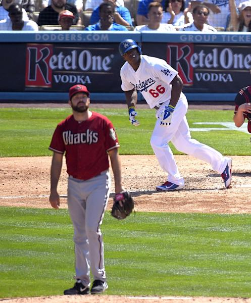 Los Angeles Dodgers' Yasiel Puig, right, hits a three-run home run as Arizona Diamondbacks relief pitcher Josh Collmenter watches the ball during the sixth inning of a baseball game, Sunday, April 20, 2014, in Los Angeles. (AP Photo/Mark J. Terrill)