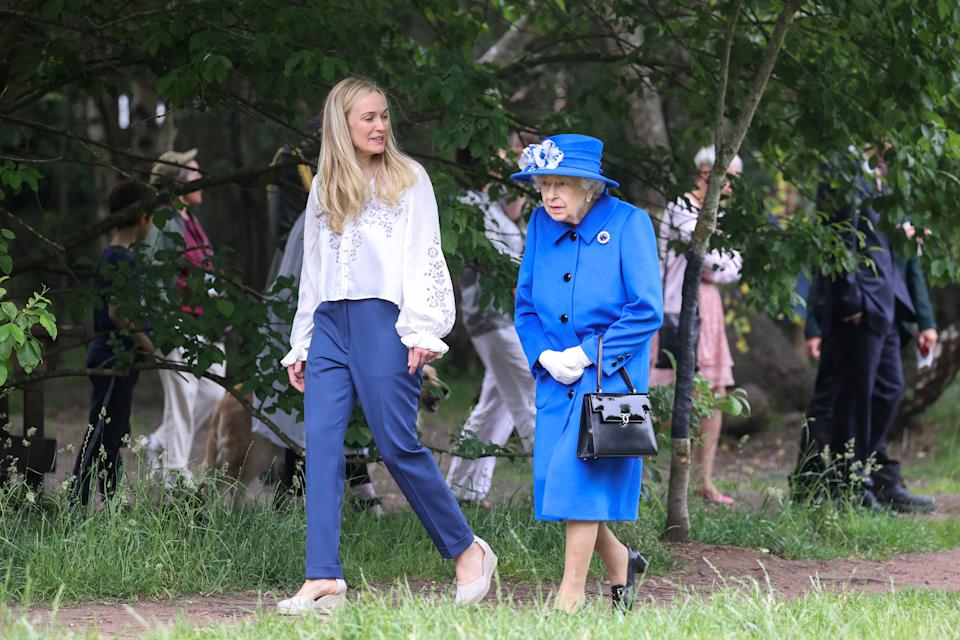 GLASGOW, SCOTLAND - JUNE 30: Queen Elizabeth II has a tour of the grounds with Director of The Children's Wood Project, Emily Cutts  during a visit to the Children's Wood Project on June 30, 2021 in Glasgow, Scotland. The Children's Wood Project is a dedicated green space designed to connect local people with nature, raise aspirations and bring the community together through outdoor activities such as gardening, beekeeping and forest schools. The Queen is visiting Scotland for Royal Week between Monday 28th June and Thursday 1st July 2021. (Photo by Chris Jackson/Getty Images)