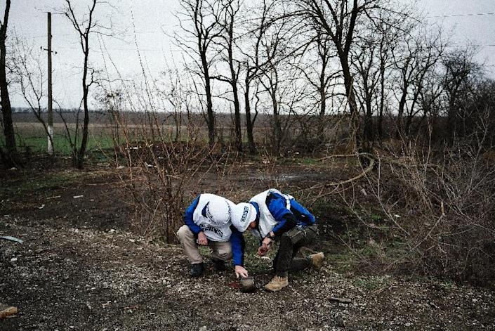 International observers of the OSCE look at a fragment of an anti-tank missile during an inspection tour near the village of Shirokino on March 30, 2015 (AFP Photo/Dimitar Dilkoff)