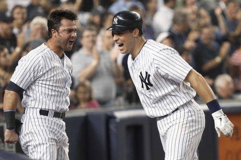New York Yankees' Mark Teixeira, right, is greeted by Nick Swisher after Teixeira hit a solo home run during the seventh inning of a baseball game against the Texas Rangers on Tuesday, Aug. 14, 2012, at Yankee Stadium in New York. Swisher and Teixeira hit back-to-back home runs in the inning. (AP Photo/Seth Wenig)