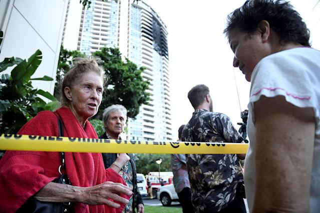 <p>Karen Hastings (L), who was evacuated from the floors where the fire broke out at Marco Polo apartment building, talks with another resident, in Honolulu, Hawaii, July 14, 2017. (Photo: Hugh Gentry/Reuters) </p>