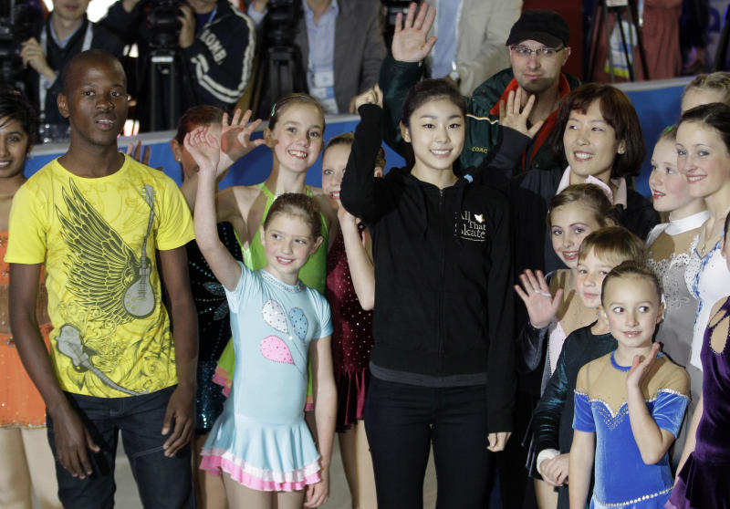 South Korea Olympic figure skater  Yu-Na Kim, center poses with young skaters during an ice skating event  in Durban, South Africa, Tuesday July 5, 2011.  The International Olympic Committee  will announce the host city for the 2018 Winter Olympics  in Durban  on July 6. The IOC members will  choose between three candidates  Annecy, France; Munich Germany; and Pyeongchang, South Korea for the 2018 host.  (AP Photo/Themba Hadebe)