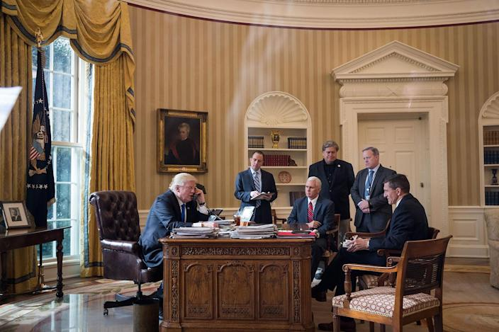 <p>JAN. 28, 2017 – President Donald Trump speaks on the phone with Russian President Vladimir Putin in the Oval Office of the White House in Washington, DC. Also pictured, from left, White House Chief of Staff Reince Priebus, Vice President Mike Pence, White House Chief Strategist Steve Bannon, Press Secretary Sean Spicer and National Security Advisor Michael Flynn. (Photo: Drew Angerer/Getty Images) </p>