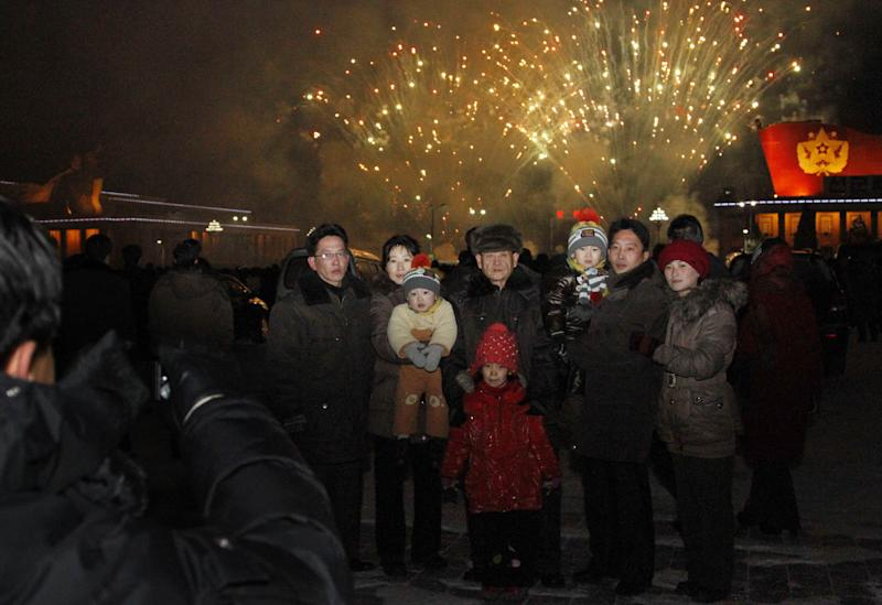 "A North Korean family has their photo taken in front of fireworks as they celebrate the new year on Tuesday Jan. 1, 2013. North Koreans celebrated the arrival of the new year, marked as ""Juche 102"" on North Korean calendars. ""Juche"" means ""self reliance,"" the North Korean ideology of independence promoted by North Korean founder Kim Il Sung, and modern-day North Korean calendars start with the year of his birth in 1912. (AP Photo/Kim Kwang Hyon)"