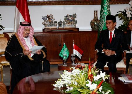 Saudi Arabia's King Salman reads documents as Indonesian President Joko Widodo looks on during their meeting at the Presidential Palace in Bogor