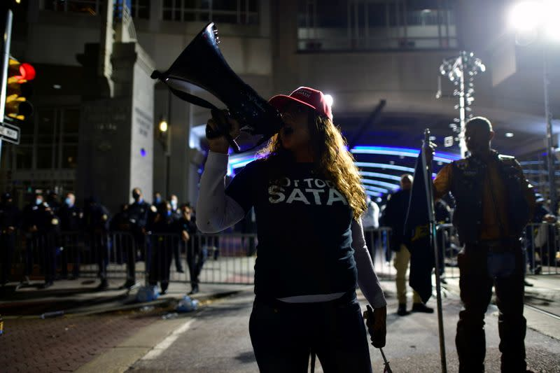 """A supporter of U.S. President Donald Trump chants """"Dead men don't vote"""" while taunting activists across the street from where votes are being counted n Philadelphia"""