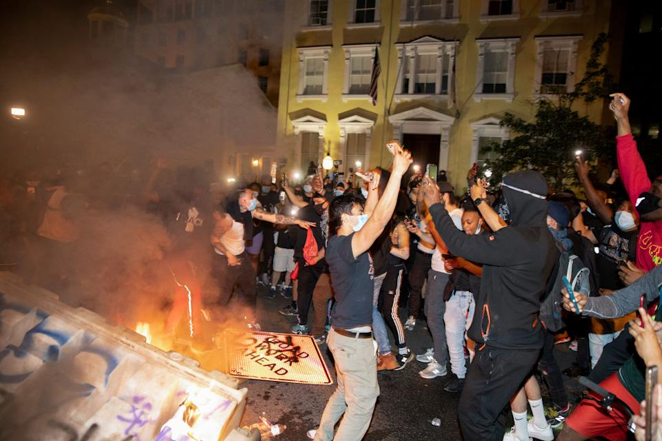 Demonstrators are seen chanting in front of a fire and graffitied signs in Washington, DC. Source: Getty Images