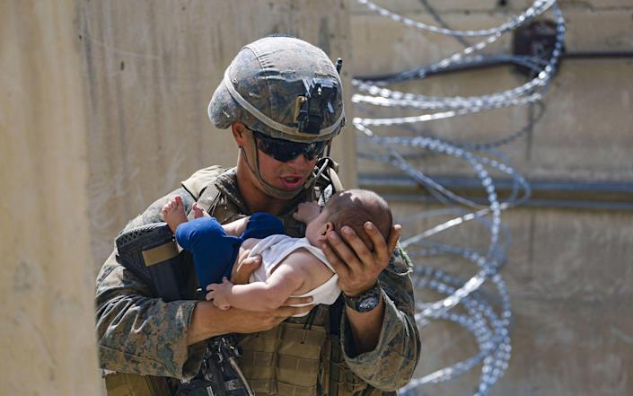 A U.S. Marine assigned to 24th Marine Expeditionary Unit (MEU) comforts an infant while they wait for the mother during an evacuation at Hamid Karzai International Airport, in Kabul on Sunday
