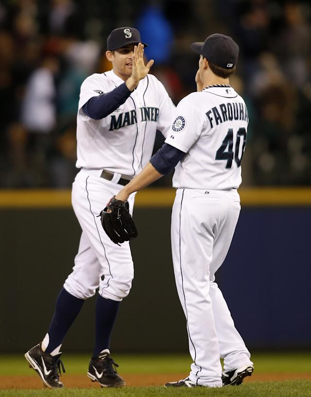 Seattle Mariners' Brad Miller, left, congratulates closing pitcher Danny Farquhar after a 7-5 win over the Oakland Athletics in a baseball game in Seattle, Saturday, Sept. 28, 2013. Miller hit a grand slam during the game. (AP Photo/John Froschauer)