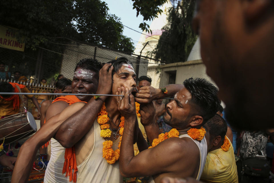 An Indian Hindu devotee reacts in pain as he gets his cheeks pierced with a steel rod as part of a ritual during an annual pilgrimage to the temple of Hindu goddess Sheetla Mata in Jammu, India, Sunday, July 25, 2021. (AP Photo/Channi Anand)