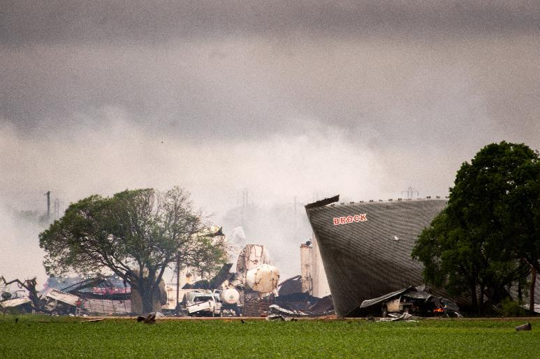 The remains of the the West Fertilizer Co. plant smolder in the rain on Thursday, April 18, 2013, in West, Texas. A massive explosion at the plant killed as many as 15 people and injured more than 160, officials said overnight. (AP Photo/Houston Chronicle, Smiley N. Pool) MANDATORY CREDIT
