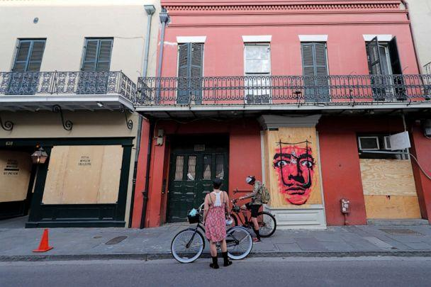 PHOTO: People on bicycles stop in front of shuttered businesses impacted by the coronavirus epidemic in the French Quarter of New Orleans, May 12, 2020. (Gerald Herbert/AP)