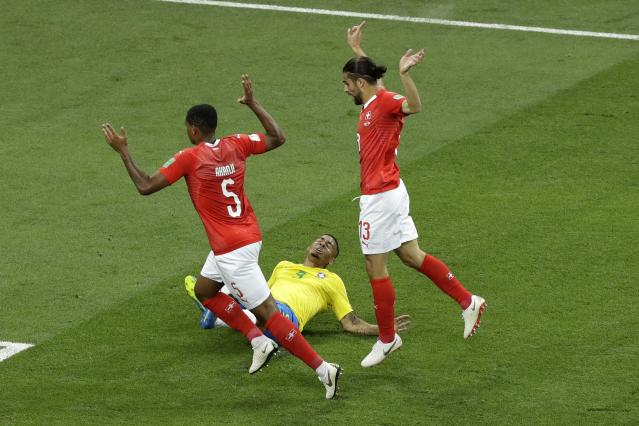 Brazil's Gabriel Jesus falls down as Switzerland's Manuel Akanji, left, and Ricardo Rodriguez hold up their hands during the group E match between Brazil and Switzerland at the 2018 soccer World Cup in the Rostov Arena in Rostov-on-Don, Russia, Sunday, June 17, 2018. (AP Photo/Andrew Medichini)